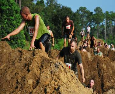 mud run make their way over a obstacle cource